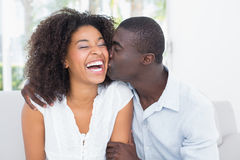 Attractive man kissing his girlfriend on the cheek Royalty Free Stock Photography