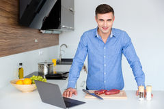 Attractive man with laptop preparing meat on the kitchen Royalty Free Stock Photo