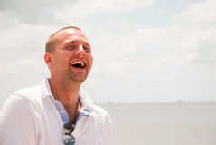 Attractive man laughing. Against blue sky Royalty Free Stock Images