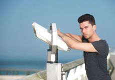 Attractive man leaning on telescope on tourism pier Stock Photo