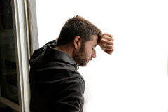 Attractive man leaning on window suffering emotional crisis and depression. Young attractive man leaning desperate on window glass at home, looking worried Stock Image