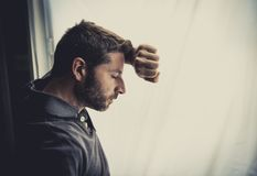 Attractive man leaning on window suffering emotional crisis and depression. Young attractive man leaning desperate on window glass at home, looking worried Stock Photography