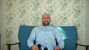 Attractive man lies on couch watching TV and holding remote. Attractive man lies on couch watching TV and holding remote. 4 k stock video