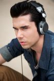 Attractive man listening to music on headphones outdoors Royalty Free Stock Images