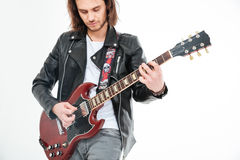 Attractive man with long hair playing electric guitar using mediator. Attractive young man with long hair playing electric guitar using mediator over white Stock Images
