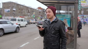 Attractive man looking at mobile phone while waiting in city bus stop. Young man looking at mobile phone while waiting in city bus stop stock footage