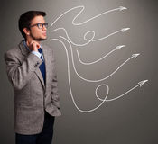 Attractive man looking at multiple curly arrows Stock Photography