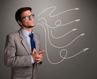 Attractive man looking at multiple curly arrows Stock Images