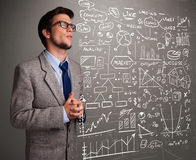 Attractive man looking at stock market graphs and symbols Royalty Free Stock Images