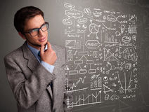 Attractive man looking at stock market graphs and symbols Stock Photo