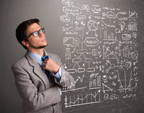 Attractive man looking at stock market graphs and symbols Royalty Free Stock Image