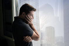 Attractive man looking through window suffering emotional crisis and depression Royalty Free Stock Images