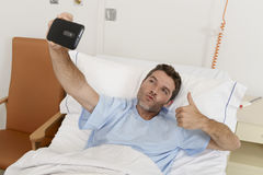 Attractive man lying on bed hospital clinic holding mobile phone taking self portrait selfie photo. Young attractive man lying on bed hospital clinic holding Stock Photography
