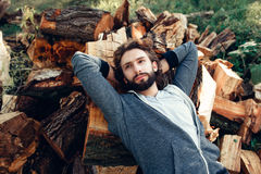 Attractive man lying on pile of wood. Portrait of attractive man lying on pile of wood. Fashion picture of very masculine guy having rest after hard work on Royalty Free Stock Photography