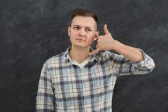 Attractive man making call me gesture. Grey studio background. Serious guy raising arm to his ear and speaking to someone stock image