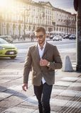 Attractive man outdoor wearing business suit jacket. Attractive man outdoor wearing elegant jacket, in European city, Turin in Italy, walking on zebra crossing Royalty Free Stock Photos