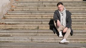 Attractive young man outdoor sitting on stone stairs. Attractive man outdoor wearing winter coat, sitting on stone stairs, in European city, Turin in Italy stock video