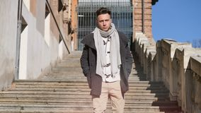 Attractive young man outdoor walking down stone stairs. Attractive man outdoor wearing winter coat, walking down stone stairs, in European city, Turin in Italy stock video