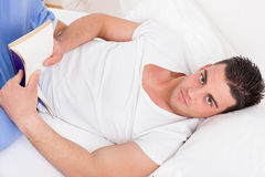 Attractive man in pajamas lying on the bed reading book royalty free stock image