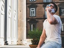 Attractive man with a phone on the background of bright, beautiful, old houses royalty free stock images