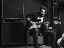 Attractive man playing an electric guitar in a studio. Black and white photo of a man with beard sitting and playing his electric guitar in a recording studio royalty free stock photo