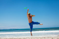 Attractive man playing frisby on beach in summer Stock Photography