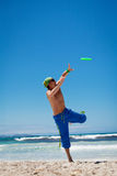 Attractive man playing frisby on beach in summer Royalty Free Stock Photos