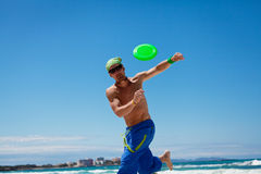 Attractive man playing frisby on beach in summer Stock Photo