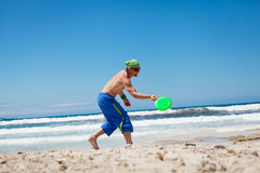 Attractive man playing frisby on beach in summer Royalty Free Stock Photo