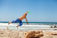Attractive man playing frisby on beach in summer Royalty Free Stock Image