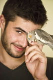 Attractive man playing with his parrot Royalty Free Stock Photography