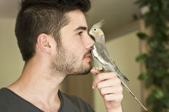 Attractive man playing with his parrot Stock Photography