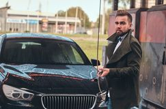 Attractive man is posing with hose at car-washing station near his car. stock photography