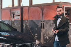 Attractive man is posing with hose at car-washing station near his car. royalty free stock photos