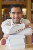 Attractive man posing in library leaning on a pile of books Stock Image