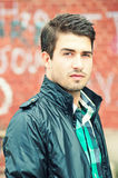 Attractive man posing outdoor over graffiti wall stock photos