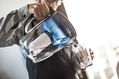 Free Attractive Man Pouring Filtered Water Into A Glass Stock Images - 153233954