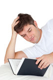 Attractive man reading a book lying on his bed Stock Photo