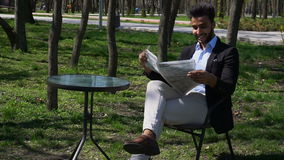 Attractive man reading newspaper in park, slow motion. Arabian guy sits on chair near table and reading newspaper in slow motion. Man dressed in blue shirt stock video
