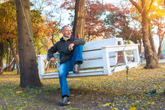 Attractive man relaxing  in a autumn park, sitting on swing and. Thinking about something. Wonderful autumn morning. Soft warm light Stock Photos