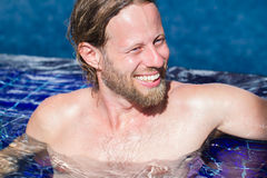 Attractive man relaxing in a pool. Attractive man relaxing in a blue swimming pool at a resort royalty free stock images