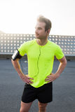 Attractive man resting after an intense workout outdoors while listening to music in headphones on his smart phone Royalty Free Stock Images