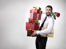 Attractive man with rose in mouth. And gifts Royalty Free Stock Photography
