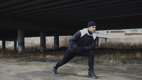 Attractive man runner doing stretching exercise for morning workout and jogging at urban location outdoors in winter Stock Images