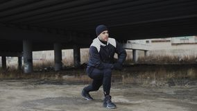 Attractive man runner doing stretching exercise for morning workout and jogging at urban location outdoors in winter Royalty Free Stock Photography