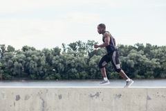 Attractive man running fast at sunset light, black man doing workout outdoors Royalty Free Stock Images
