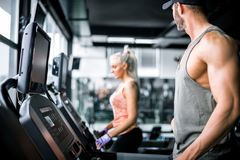 Attractive man running on treadmill and looking at girl Royalty Free Stock Photography