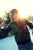 Attractive man screaming outside in winter. Handsome young man with ear flap hat screaming outside in winter with beautiful sunlight behind him Stock Image