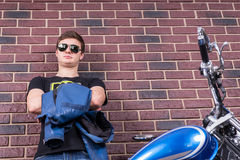 Attractive Man in Shades with Jacket and Motorbike Royalty Free Stock Photos