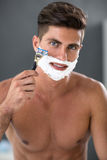 Attractive  man shaving in the bath Stock Image